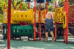 Garçon drôle d'enfant ayant l'amusement avec l'oscillation à chaînes sur le terrain de jeu extérieur Image stock