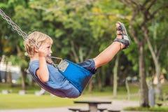 Garçon drôle d'enfant ayant l'amusement avec l'oscillation à chaînes sur le terrain de jeu extérieur enfant balançant le jour cha Photo stock