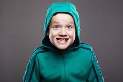 Garçon drôle dans le capot enfant d'émotion de grimace image libre de droits