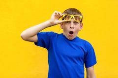Garçon drôle en verres de couleur regardant l'appareil-photo et choqués Images stock