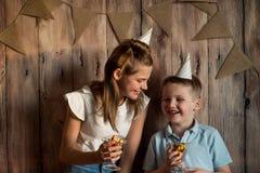Garçon drôle et fille mangeant du maïs éclaté, riant d'une partie fond en bois avec des drapeaux, fête d'anniversaire gaie Images libres de droits