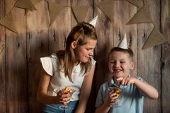 Garçon drôle et fille mangeant du maïs éclaté, riant d'une partie fond en bois avec des drapeaux, fête d'anniversaire gaie Image libre de droits