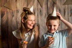 Garçon drôle et fille mangeant du maïs éclaté, riant d'une partie fond en bois avec des drapeaux, fête d'anniversaire gaie Photos libres de droits