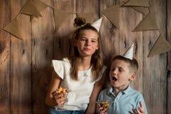 Garçon drôle et fille mangeant du maïs éclaté, riant d'une partie fond en bois avec des drapeaux, fête d'anniversaire gaie Photo stock