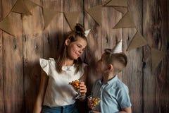Garçon drôle et fille mangeant du maïs éclaté, riant d'une partie fond en bois avec des drapeaux, fête d'anniversaire gaie Images stock