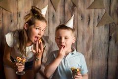 Garçon drôle et fille mangeant du maïs éclaté, riant d'une partie fond en bois avec des drapeaux, fête d'anniversaire gaie Photographie stock libre de droits