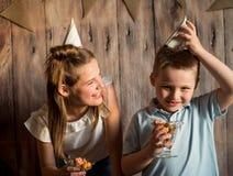 Garçon drôle et fille mangeant du maïs éclaté, riant d'une partie fond en bois avec des drapeaux, fête d'anniversaire gaie Photos stock