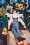 Garçon drôle d'ange de tilda s'asseyant sur des cadeaux de nouvelle année Photo libre de droits