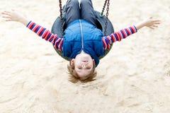 Garçon drôle d'enfant ayant l'amusement avec l'oscillation à chaînes sur le terrain de jeu extérieur Image libre de droits