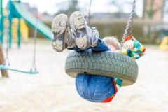 Garçon drôle d'enfant ayant l'amusement avec l'oscillation à chaînes sur le terrain de jeu extérieur Photo libre de droits