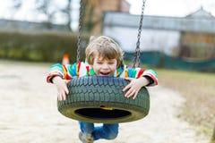 Garçon drôle d'enfant ayant l'amusement avec l'oscillation à chaînes sur le terrain de jeu extérieur Photos libres de droits