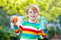 Garçon drôle d'enfant d'école avec la bouteille de livres, de pomme et de boissons Image libre de droits