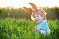 Garçon drôle de 3 ans avec des oreilles de lapin de Pâques, célébrant Pâques Images stock