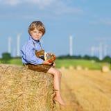 Garçon drôle de petit enfant s'asseyant sur la pile de foin et mangeant le bretzel Photographie stock libre de droits