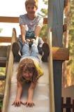 Garçon drôle et fille jouant sur le terrain de jeu Image libre de droits