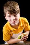 Garçon drôle mangeant le sandwich Image stock