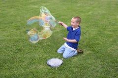 Garçon effectuant des bulles de savon Photographie stock libre de droits