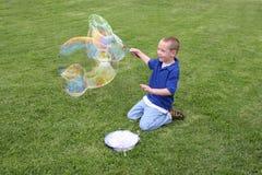 Garçon effectuant des bulles de savon Images stock