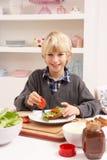 Garçon effectuant le sandwich dans la cuisine Photographie stock libre de droits