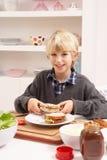 Garçon effectuant le sandwich dans la cuisine Image libre de droits