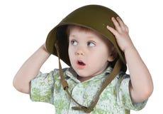 Garçon effrayé avec le casque d'armée d'isolement sur le blanc Photographie stock libre de droits