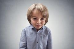 Garçon effronté mignon avec l'expression coupable photo stock