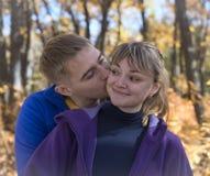 Garçon embrassant la fille dans la forêt d'automne Photographie stock