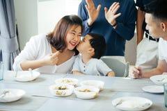 Garçon embrassant la mère sur des joues avec la famille asiatique de totalité de trois générations ensemble à la maison Images libres de droits