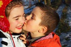 Garçon embrassant une fille, coeurs autour Images stock
