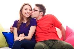 Garçon embrassant une fille sur le sofa à la maison Photo libre de droits