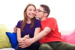Garçon embrassant une fille sur le sofa à la maison Photographie stock libre de droits