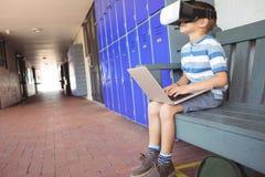 Garçon employant des verres d'ordinateur portable et de réalité virtuelle tout en se reposant sur le banc dans le couloir photo stock
