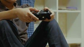 Garçon employant un contrôleur pour jouer un jeu vidéo Photos libres de droits