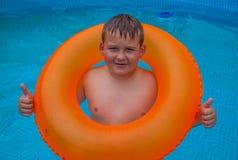 Garçon en ayant l'amusement dans la piscine photos stock