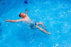 Garçon en ayant l'amusement dans la piscine images stock
