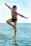 Garçon en bonne santé sautant dans l'eau Photos stock