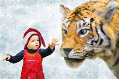 Garçon en chapeau de Noël et collage de tigre Photos stock