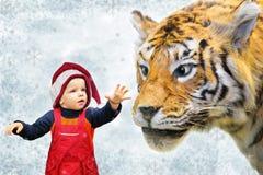 Garçon en chapeau de Noël et collage de tigre Photos stock