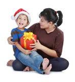 Garçon en chapeau du père noël et sa maman Image stock