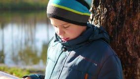Garçon en parc d'automne près du lac lisant un livre Un bel horizontal d'automne Éducation d'école banque de vidéos
