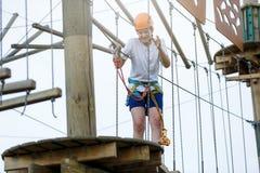 Garçon en parc d'aventure de forêt Enfant dans le casque orange et montées blanches de T-shirt sur la haute traînée de corde S'él image libre de droits