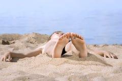 Garçon en sable sur le bord de la mer Photos stock