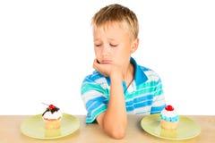 Garçon ennuyé et deux petits gâteaux Photographie stock libre de droits