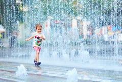 Garçon enthousiaste courant entre l'écoulement d'eau en parc de ville Photographie stock libre de droits