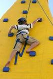 Garçon escaladant un mur s'élevant. image libre de droits