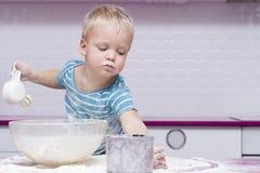 Garçon espiègle d'enfant avec la vaisselle de cuisine et produits alimentaires faisant la pâtisserie Photo libre de droits