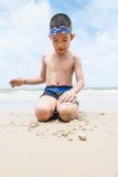 Garçon espiègle sur la plage avec la mer sur le fond. Image stock