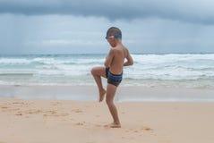 Garçon espiègle sur la plage avec la mer sur le fond. Images stock