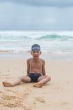 Garçon espiègle sur la plage avec la mer sur le fond. Photo stock
