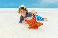 Garçon et étoiles de mer sur une plage tropicale Photo stock